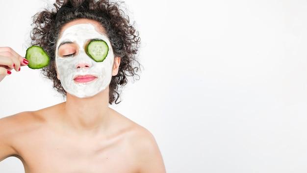 Mujer joven con cosméticos en la cara que aplica el pepino a su ojo