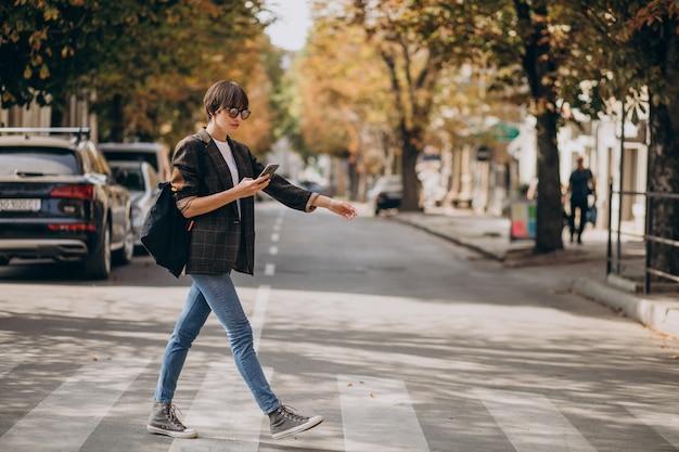 Mujer joven, cruzar la calle, y, utilizar, teléfono