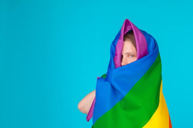 Mujer joven cubierta con la bandera del orgullo lgbt