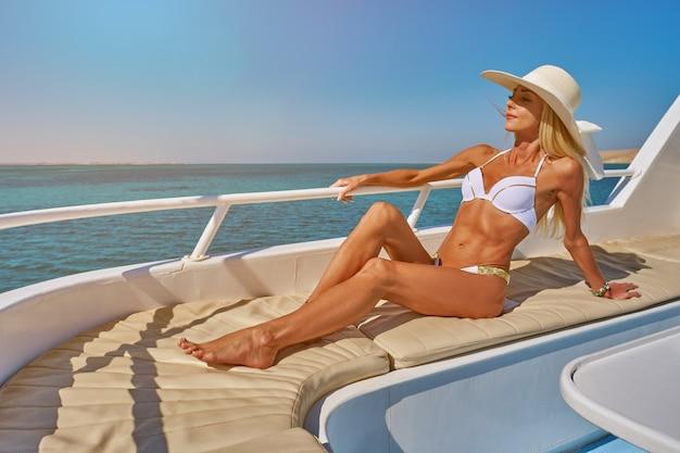 Mujer joven en la cubierta de un barco en mar abierto en un día soleado de verano
