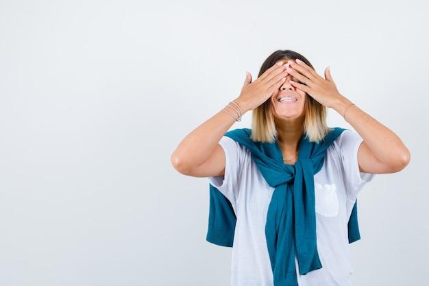 Mujer joven cubriendo los ojos con las manos en camiseta blanca y mirando feliz, vista frontal.