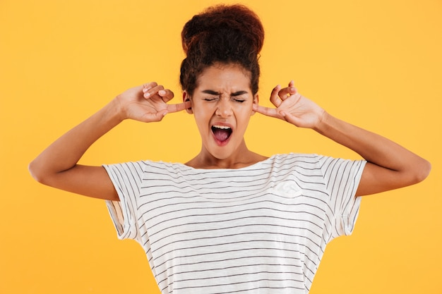 Mujer joven cubriendo sus oídos para no escuchar