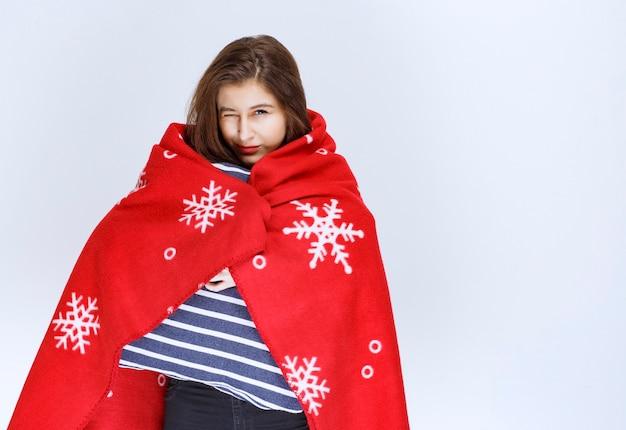 Mujer joven cubriéndose con una cálida manta roja y sosteniendo una manta de rayas azules.