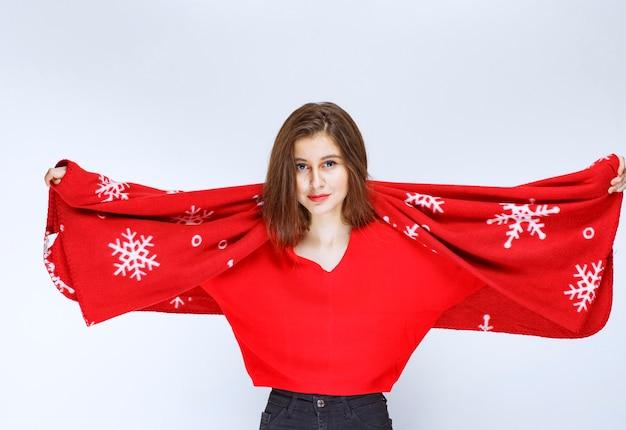 Mujer joven cubriéndose con una cálida manta roja.