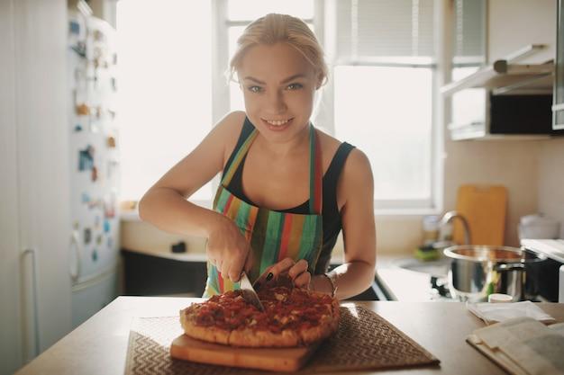 Mujer joven con un cuchillo corta la pizza