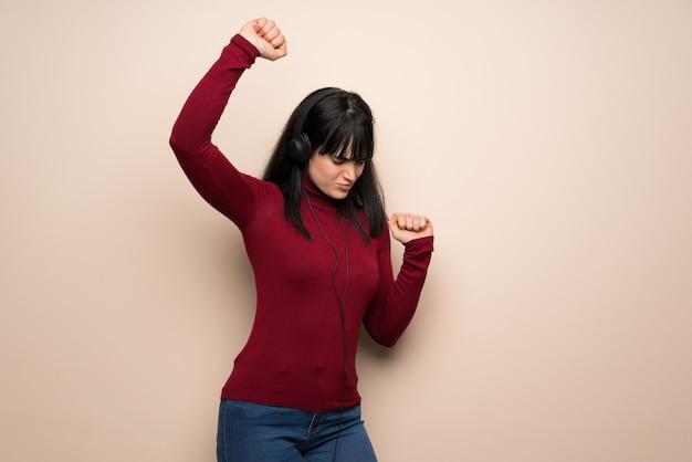 Mujer joven con cuello alto rojo escuchando música con auriculares y bailando