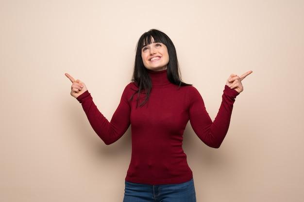 Mujer joven con cuello alto rojo que señala con el dedo índice una gran idea