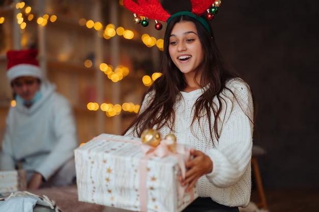Mujer joven con cuernos abriendo caja de regalo de navidad