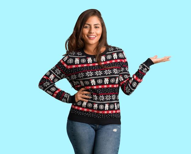 Mujer joven de cuerpo completo con un jersey de navidad sosteniendo algo con la mano