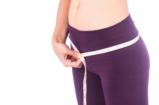 Mujer joven con cuerpo delgado midiendo caderas