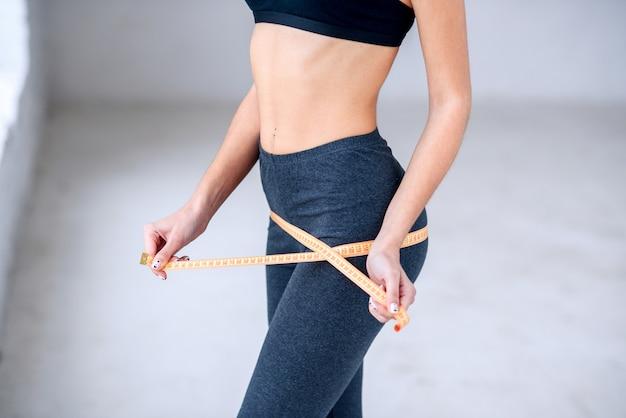 Mujer joven con cuerpo de gimnasio atractivo con cinta métrica en las manos.
