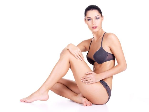 Mujer joven con cuerpo sano y piernas largas y delgadas se sienta en la pared blanca