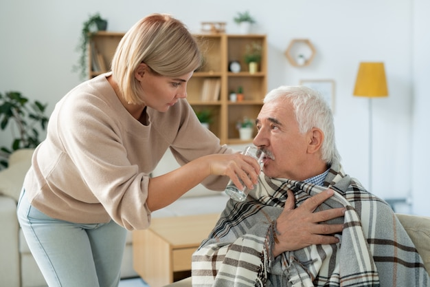 Mujer joven cuidadosa cuidando a su padre mayor enfermo envuelto en cuadros mientras le da un vaso de agua
