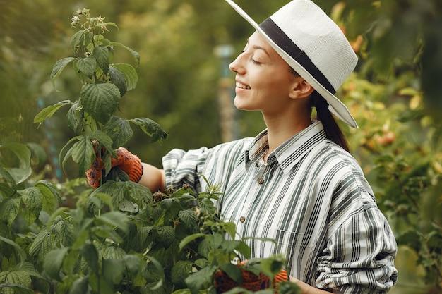 Mujer joven cuidando plantas. morena con sombrero y guantes.