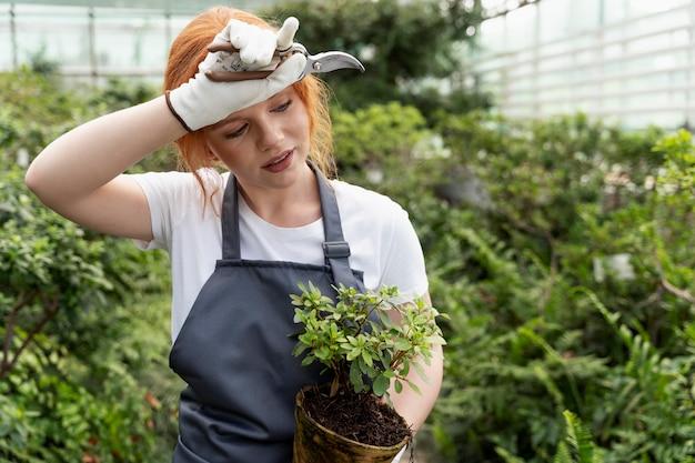 Mujer joven cuidando sus plantas en invernadero