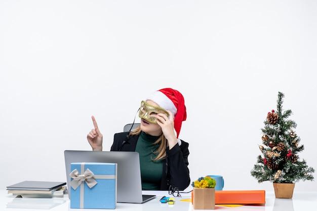 Mujer joven curiosa con sombrero de santa claus sosteniendo anteojos y con máscara sentado en una mesa con un árbol de navidad y un regalo en la oficina sobre fondo blanco.