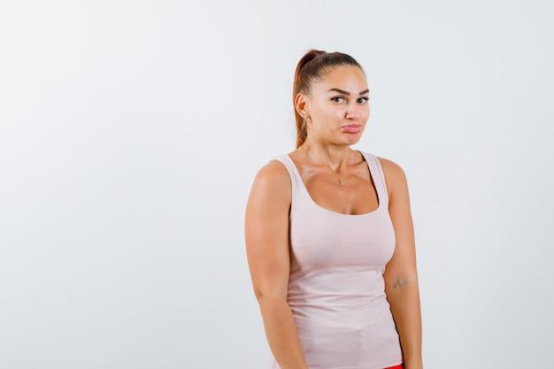 Mujer joven curvándose los labios en camiseta y mirando vacilante, vista frontal.