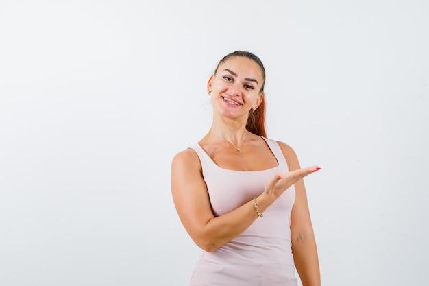 Mujer joven dando la bienvenida en camiseta y con aspecto enérgico. vista frontal.