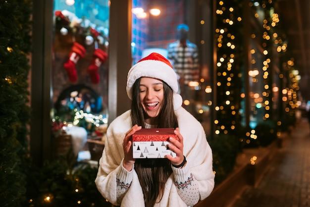 Mujer joven dando caja para usted al aire libre en la calle de invierno concepto de intercambio de regalos.