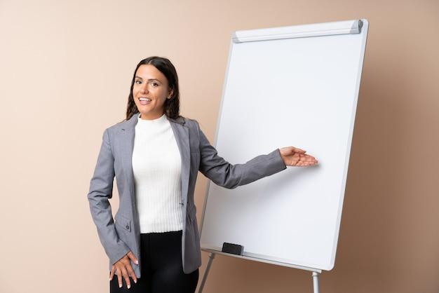 Mujer joven dando una presentación en la pizarra blanca dando una presentación en la pizarra blanca y señalando