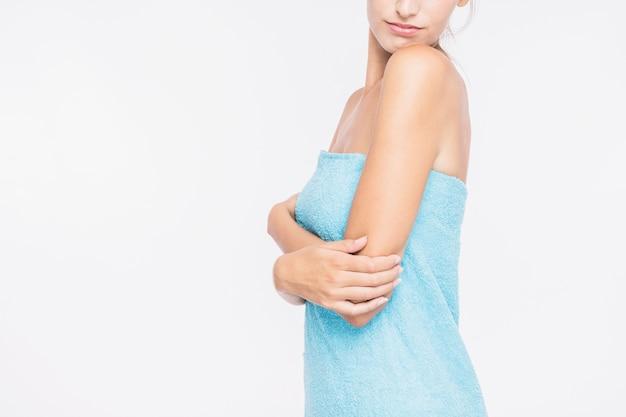 Mujer joven de pie en una toalla azul
