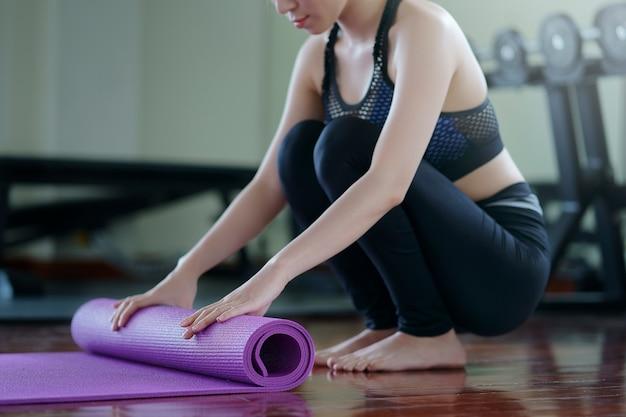 Mujer joven de yoga rodando su estera después de una clase de yoga en el gimnasio