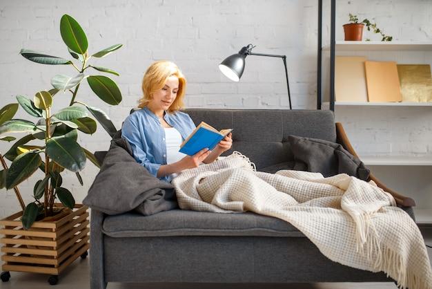 Mujer joven debajo de una manta leyendo un libro en el acogedor sofá amarillo, salón en tonos blancos