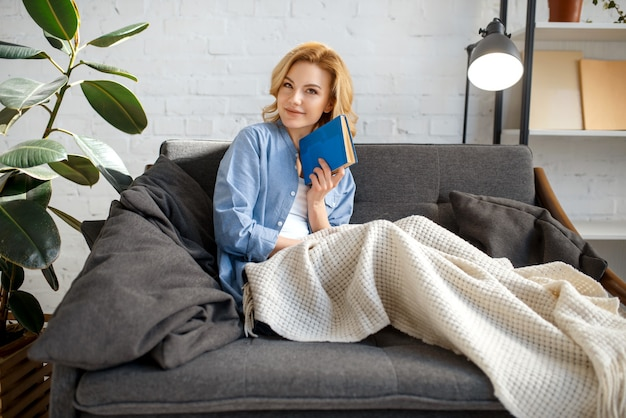 Mujer joven, debajo, un, manta, libro de lectura, en, sofá