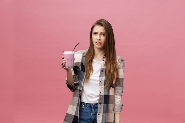 Mujer joven decepcionada beber jugo de batido. retrato aislado