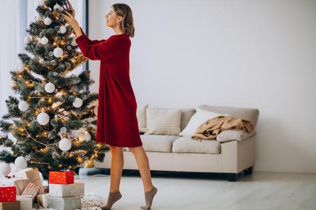 Mujer joven decorar el árbol de navidad