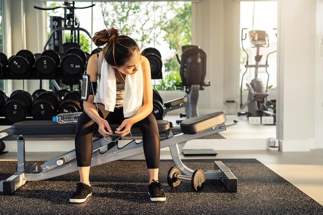 Mujer joven del deporte en el gimnasio, la aptitud, el concepto de estilo de vida de entrenamiento