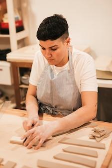 Mujer joven en delantal cortando la arcilla con herramientas en mesa de madera