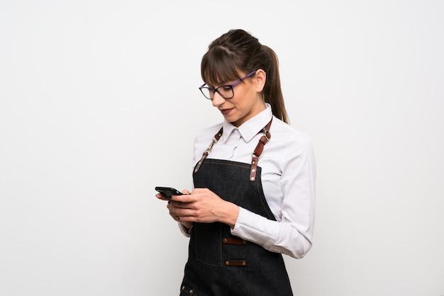 Mujer joven con delantal enviando un mensaje con el móvil.