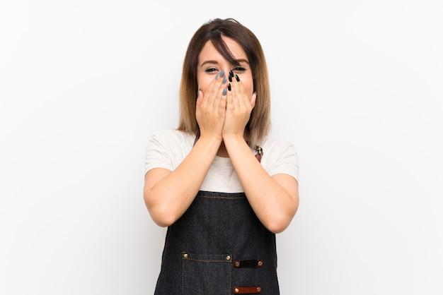 Mujer joven con un delantal con expresión facial sorpresa.