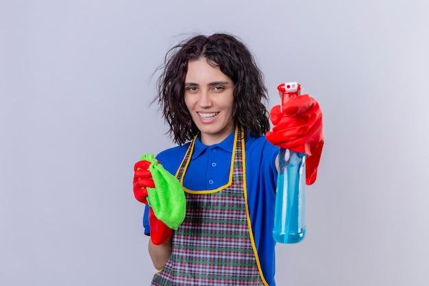 Mujer joven con delantal y guantes de goma con alfombra y spray de limpieza divirtiéndose, sonriendo alegremente sobre la pared blanca