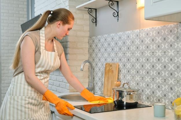 Mujer joven en delantal guantes limpiando la cocina después de cocinar
