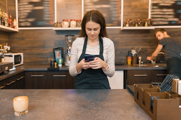 Mujer joven en delantal trabajador de cafetería en bar counte