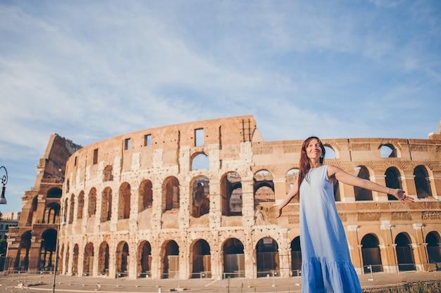 Mujer joven delante del coliseo en roma, italia