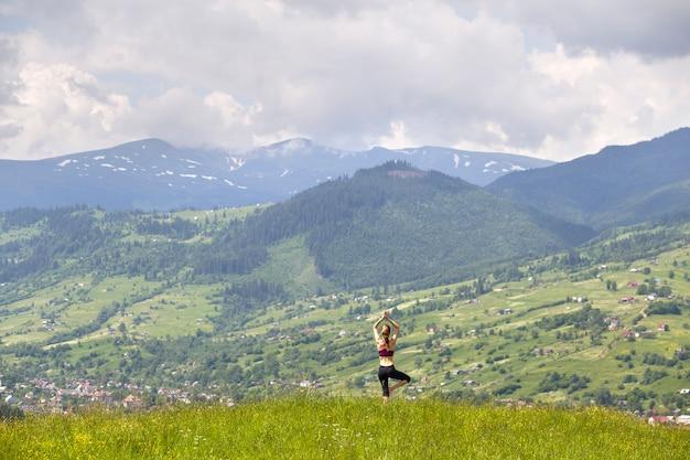 La mujer joven delgada atractiva que hace yoga ejercita al aire libre en fondo de montañas verdes en día de verano soleado.
