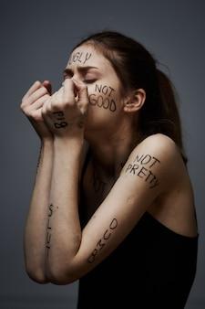 Mujer joven delgada con insultos en las inscripciones del cuerpo, malas palabras, estado depresivo, soledad