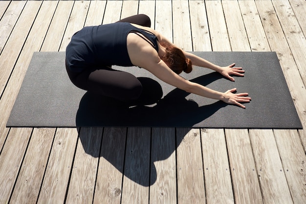 Mujer joven delgada meditando, relajándose y practicando yoga en el muelle de madera cerca del lago.