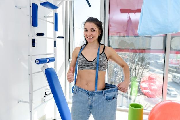 Mujer joven delgada en la parte superior midiendo su pecho en el gimnasio. concepto de estilo de vida saludable
