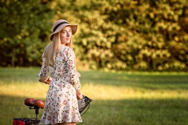 Mujer joven, delgada, rubia en bicicleta contra el paisaje del parque desenfocado. sombra de color otoñal.