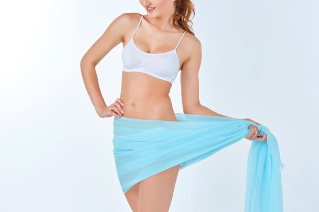 Mujer joven, delgada, sana y hermosa en lencería blanca con mantón azul aislado en el fondo blanco