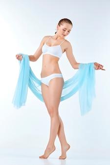 Mujer joven, delgada, sana y hermosa en lencería blanca