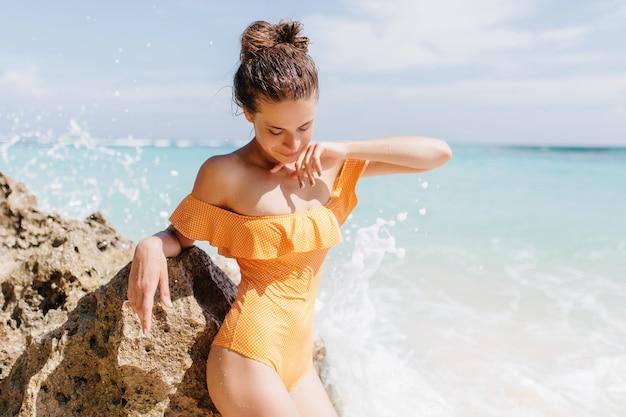 Mujer joven delgada en traje de baño amarillo hermoso mirando hacia abajo mientras posa en la playa. magnífica chica caucásica tomando el sol en la orilla del mar.