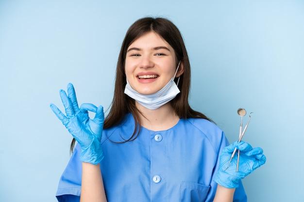 Mujer joven dentista con herramientas sobre la pared azul que muestra un signo bien con los dedos