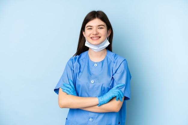 Mujer joven dentista con herramientas sobre pared azul