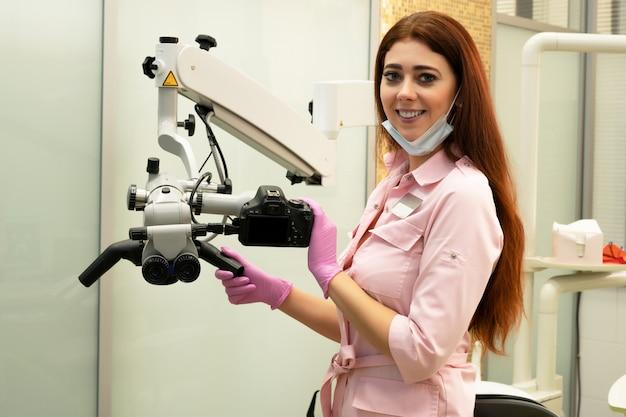 Mujer joven dentista y microscopio profesional en clínica dental