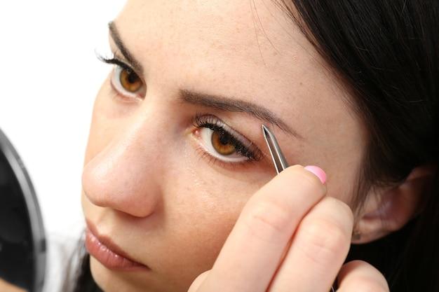 Mujer joven depilarse las cejas con pinzas de cerca